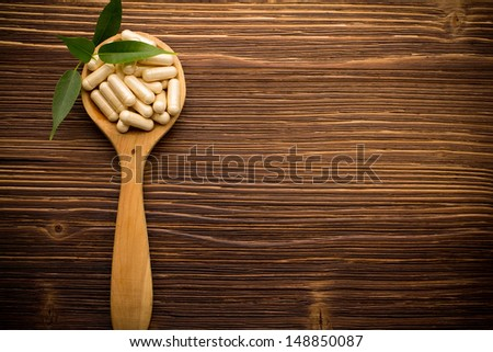 Vitamin capsules in a wooden spoon on a wooden background. - stock photo