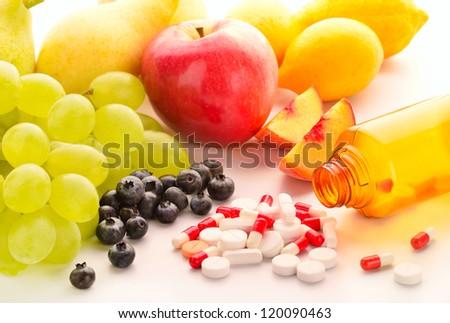 Vitamin pills with fresh fruits - stock photo