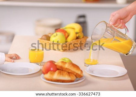 Vitamin refreshment. Caring father is busy with pouring juice for him and his small son.  - stock photo