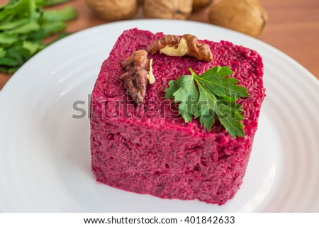 Vitamin salad of boiled beets in the form of a square, with walnuts on a white plate - stock photo