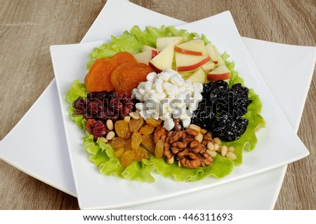 Vitamin salad with nuts, apples, dried fruit and cottage cheese in lettuce leaves - stock photo