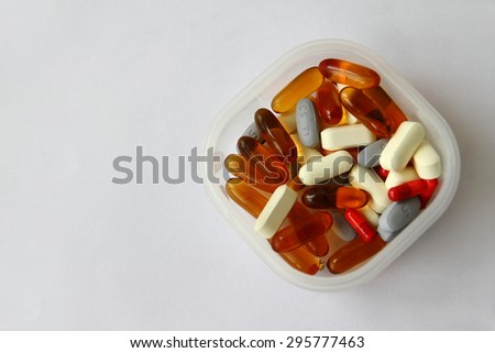 Vitamin tablets, fish oil capsules and other supplements in a box isolated on white background - stock photo