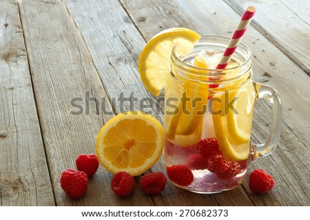 Vitamin water with lemon and raspberries in a jar with straw against a wood background - stock photo