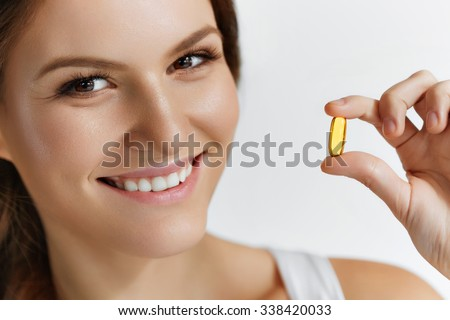 Vitamins. Close Up Of Happy Beautiful Girl With Pill With Cod Liver Oil Omega-3. Nutrition. Healthy Lifestyle. Nutritional Supplements. Sport, Diet Concept. Vitamin D, E, A Fish Oil Capsules. - stock photo