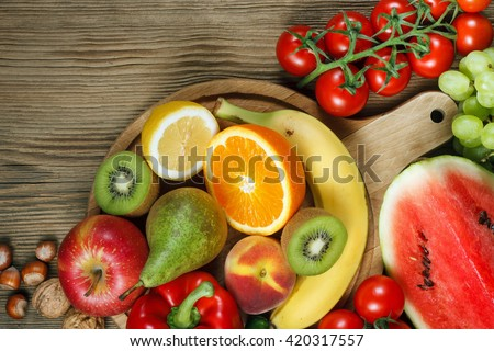 Vitamins in fruits and vegetables. Natural products rich in vitamins as oranges, lemons, red pepper, kiwi,tomatoes, bananas, pears, apples, walnuts, watermelon, hazelnuts, peach and green grape - stock photo