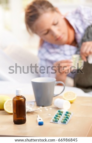 Vitamins, medicines, hot tea and lemons in front, woman caught cold taking medicines in background.? - stock photo