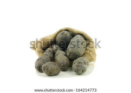 Vitelotte noir or purple potato in a burlap bag. On a white background. - stock photo