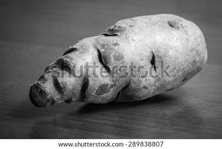 Vitelotte on wooden table, black and white image - stock photo