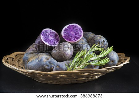 Vitelotte or blue-violet potatoes on a black background - stock photo