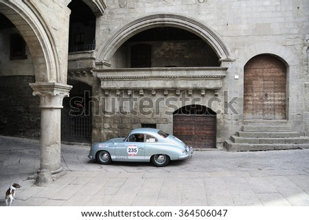 VITERBO (VT), ITALY - MAY 16: A light blue Porsche 356 1500 Super takes part to the 1000 Miglia classic car race on May 16, 2015 in Viterbo (VT). The car was built in 1952; a dog looks at. - stock photo