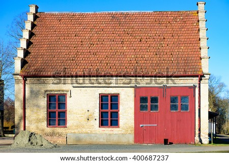 Vittskovle, Sweden - April 1, 2016: An old storage building with interesting architectural details. Large vehicle door and two windows on the facade. Interesting roof endings. - stock photo