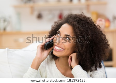 Vivacious beautiful young African American lady with an afro hairstyle chatting on her mobile listening to a call with a wide beaming smile of delight - stock photo
