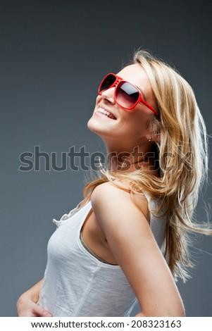 Vivacious beautiful young blond woman with a lovely smile leaning back looking up into the air with a happy expression, profile view on grey - stock photo