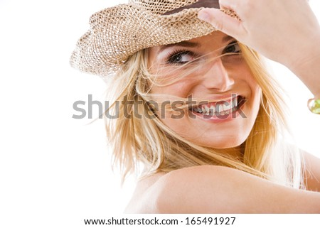Vivacious healthy beautiful blond woman with a lovely playful smile and windblown long blond hair holding onto a trendy straw hat as she looks back over her shoulder, on white - stock photo