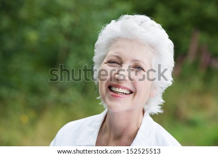 Vivacious laughing grey haired senior woman outdoors in a lush green park, close up portrait - stock photo