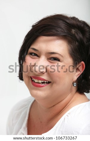 Vivacious laughing overweight woman smiling spontaneously as she enjoys life to the full - stock photo