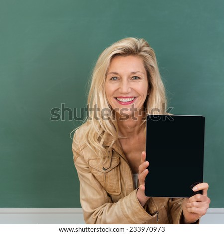 Vivacious stylish middle-aged teacher displaying a blank tablet as she stands in front of the chalkboard - stock photo
