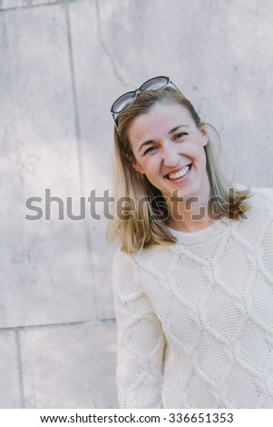 Vivacious trendy blond woman with a friendly smile standing against a white stone wall outdoors laughing at the camera, copyspace above - stock photo