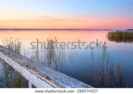 Vivid and colourful sunset at Long Jetty and reflections on Tuggerah Lake NSW Australia. A beautiful place to unwind and relax - stock photo