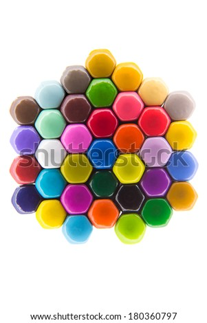 Vivid pattern in the colors of the rainbow created by the tightly packed hexagonal backs of colored pencil crayons isolated on white in an art and creativity concept - stock photo