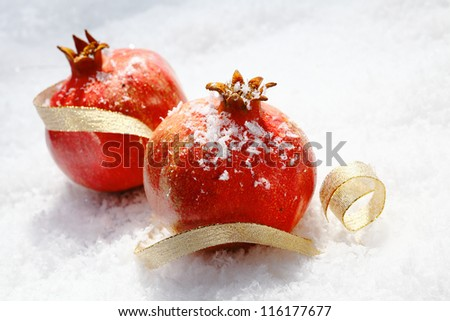 Vivid red Christmas pomegranates dusted with snowflakes lying in fresh winter snow with a decorative gold ribbon - stock photo