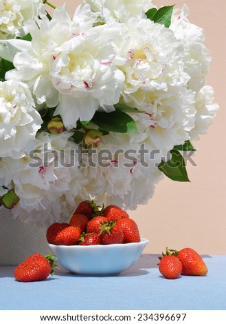Vivid red juicy sweet strawberries in saucer on the background of a lush bouquet of peonies in delicate white vase with space for text on blue tablecloth - stock photo