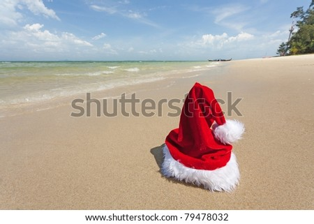 vivid santa hat standing on tropical beach - stock photo