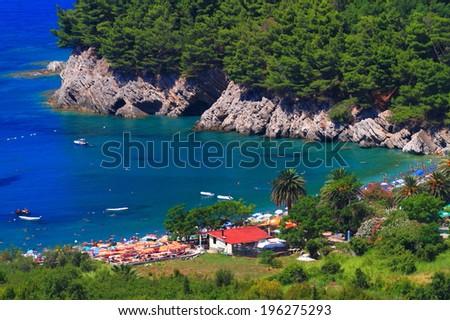 Vivid vegetation surrounds a small beach near the Adriatic sea  - stock photo
