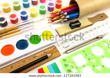 Vividly colorful art supplies and drafting implements on a white background - stock photo
