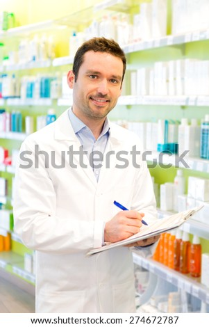 Vjew of a Attractive pharmacist taking notes at work - stock photo
