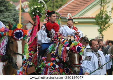 VLCNOV, CZECH REPUBLIC - MAY 26, 2013: Young men dressed in traditional folk costume ride horses during the Ride of the Kings folklore festival in Vlcnov, South Moravia, Czech Republic. - stock photo