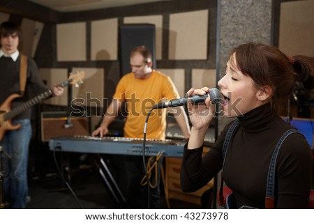vocalist girl is singing. electrical guitar player and keyboarder in out of focus - stock photo