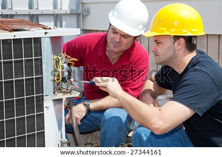 Vocational student learns air conditioning repair from an experienced instructor. - stock photo