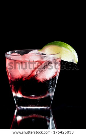 vodka and cranberry served on the rocks isolated on a black background on a reflective surface garnished with a fresh lime slice - stock photo