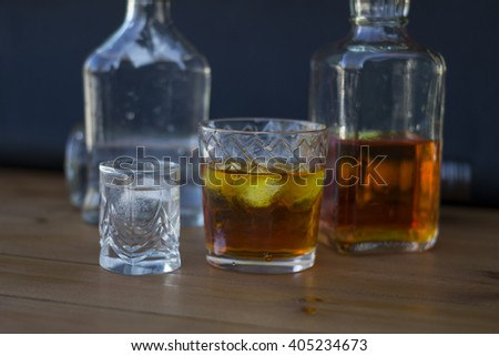 Vodka and whiskey in the bottle, vodka and whiskey in glass with ice, alcoholic drink - stock photo