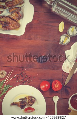 Vodka, gin, tequila in a glass with ice, fried chicken legs and fried chicken wings , Cherry tomatoes, Spices, Italian food . top view, closeup - stock photo