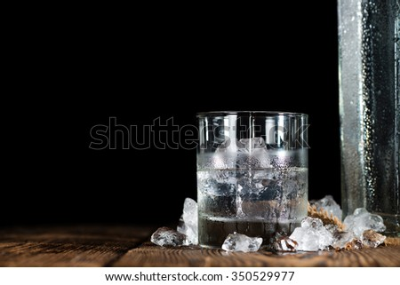 Vodka on the rocks (on an old wooden table) as detailed close-up shot - stock photo