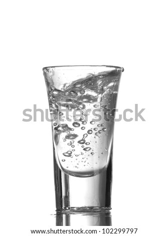 Vodka poured into a glass isolated on white - stock photo