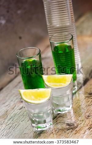 Vodka with lemon, bottle and green liquor - stock photo
