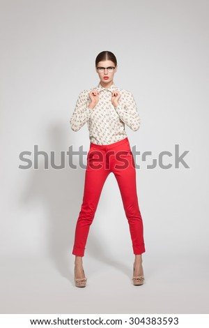 Vogue concent of woman in red trousers. Full length portrait of trendy hipster girl standing at the white wall background. - stock photo