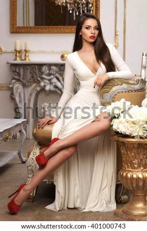 Vogue fashion style portrait of young beautiful pretty elegant rich woman wearing evening dress and sitting on armchair in luxury apartments - stock photo