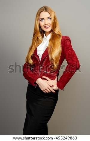 Vogue shot of a beautiful elegant young woman in over grey background. Business style clothes. - stock photo