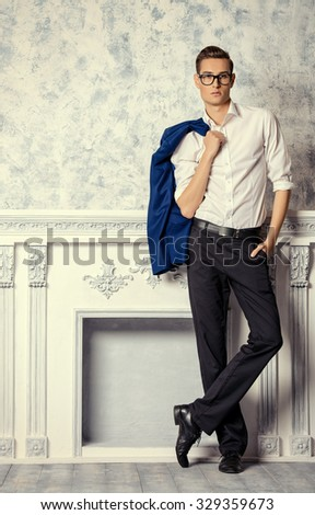 Vogue shot of a handsome elegant man in a suit posing in vintage interior. Men's beauty, fashion. - stock photo