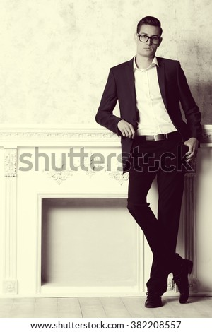 Vogue shot of a handsome elegant man in a suit posing in vintage interior. Men's beauty, fashion. Sepia. - stock photo