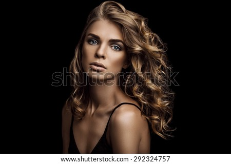 Vogue style close-up portrait of beautiful woman with long curly blond hair on black background - stock photo