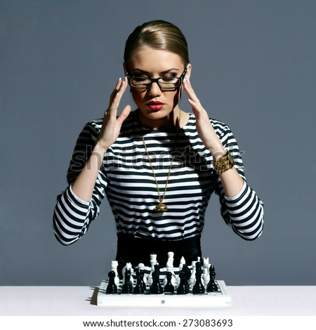 Vogue style fashion portrait of young pretty stylish girl or female model sitting with chess and thinking. Fashionable woman in striped blouse or frock - stock photo