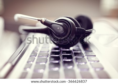 VOIP headset on laptop computer keyboard concept for communication, it support, call center and customer service help desk - stock photo