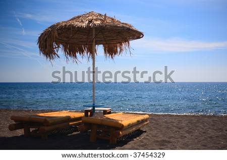 Volcanic beach. Two sun beds on volcanic black sand beach in Greece. - stock photo