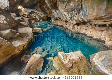 Volcanic cave Grjotagja with a incredibly blue and hot thermal water near lake Myvatn in the northeastern Iceland - stock photo