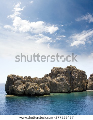 Volcanic island in blue sea. White clouds and blue sky. Vertical composition - stock photo
